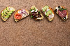 A set of various sandwiches with salmon, smoked sausage, vegetables and feta cheese on a brown stone background. Top view royalty free stock images