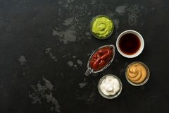 Set of various sauces in bowls on a black stone background. Mustard sauce, tomato, wasabi, mayonnaise, soy. Top view, copy space stock photo