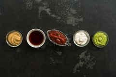 Set of various sauces in bowls in a row on a black stone background. Mustard sauce, tomato, wasabi, mayonnaise, soy. , Top view, stock photos