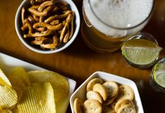 Set of various snacks, pint of lager beer in a glass, a standard set of drinking and eating in a pub. Beer and snacks stock images