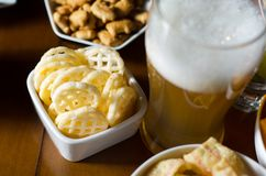 Set of various snacks, pint of lager beer in a glass, a standard set of drinking and eating in a pub. Beer and snacks royalty free stock photo