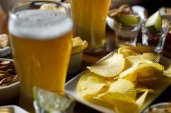Set of various snacks, pint of lager beer in a glass, a standard set of drinking and eating in a pub. Beer and snacks stock image