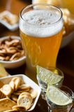 Set of various snacks, pint of lager beer in a glass, a standard set of drinking and eating in a pub. Beer and snacks royalty free stock image