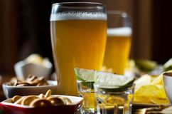 Set of various snacks, pint of lager beer in a glass, a standard set of drinking and eating in a pub. Beer and snacks stock photo