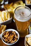 Set of various snacks, pint of lager beer in a glass, a standard set of drinking and eating in a pub. Beer and snacks royalty free stock photography