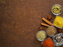 Set of various spices on a dark brown rusty metal table - coriander seeds, ground red pepper, salt, black. Pepper, rosemary, turmeric, curry, coriander, star stock photography