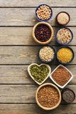 A set of various superfoods , whole grains,beans, seeds, legumes in bowls on a wooden plank table. Top view, copy space.  royalty free stock image
