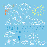 Set of various unique clouds and weather signs on blue background. Hand drawn clouds. Marker stroke sky with sun and Royalty Free Stock Image