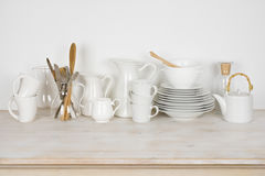Set of various white dishware and cutlery on wooden table Royalty Free Stock Photography