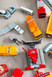 Set of various yellow, red and white car toy on grey wooden background. Top view. Collection. Stock Photos