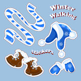 Set of vector stickers about the winter holidays and walks in the fresh air. Striped blue scarf, a warm hat with pom-poms and patt. Ern, knit mittens with Stock Photography