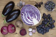 Set of vegetables and berries on aged wooden background: onion, eggplant, cabbage, beetroot, garlic, basil, grape, black currant. Royalty Free Stock Photos