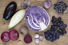 Set of vegetables and berries on aged wooden background: onion, eggplant, cabbage, beetroot, garlic, grape, black currant. Stock Photography