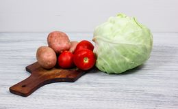 Set of vegetables cabbage potatoes on a wooden table background. Set of vegetables cabbage potatoes carrots onion garlic parsley dill beet ginger on a wooden Royalty Free Stock Photos