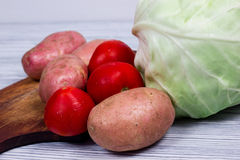 Set of vegetables cabbage potatoes on a wooden table background. Set of vegetables cabbage potatoes carrots onion garlic parsley dill beet ginger on a wooden Stock Images