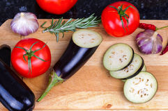 Set of vegetables on cutting board, eggplant,. Set of vegetables on cutting board eggplant garlic tomatoes rosemary chili pepper Royalty Free Stock Images