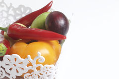 A set of vegetables for salad lies in a lace basket. On a white background. Onions and tomatoes of different colors Stock Photos