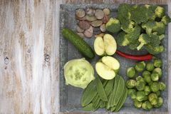 Set of vegetables on white painted plate and wooden background: kohlrabi, cucumber, apple, pepper, brussels sprouts, pea pods, bro Stock Photos