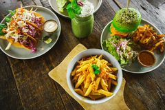 Set of vegetarian dishes on a wooden table top view. Pasta, green burger, falafel, shaurma, lavash from spirulina stock photography