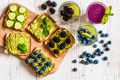 Set of vegetarian toast sandwiches with avocado and drinks. Variety of healthy food and drinks on white wooden Royalty Free Stock Photography