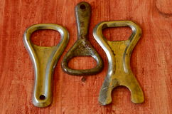 Set of vintage bottle openers on brown wooden background.  stock images
