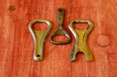 Set of vintage bottle openers on brown wooden background.  stock photos