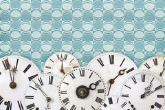 Set of vintage clock faces against a retro wallpaper background Stock Photos