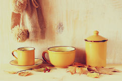 Set of vintage coffee mugs and jar over rustic textured wooden table and autumn leaves. image is retro filtered Royalty Free Stock Images
