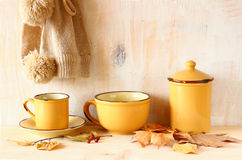 Set of vintage coffee mugs and jar over rustic textured wooden table and autumn leaves. image is retro filtered. Royalty Free Stock Photography