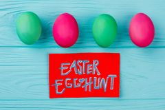 Set of vintage colors eggs and card. Red paper card with text Easter egg hunt on blue wooden background. Easter traditions and history stock image