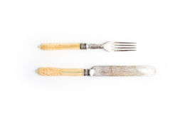 Set of vintage dinnerware. Knife and fork with bone handles on a white background. Top view. Set of vintage dinnerware. Knife and fork with bone handles on a stock photo