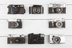 Set of vintage film cameras on wooden table Stock Photos