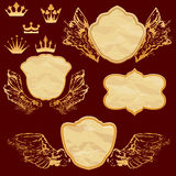 Set of vintage labels in shield shapes with old paper grunge tex. Ture, golden wings and crown Stock Photography