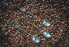 Set of vintage silver spoons on a background of coffee beans. Set of vintage silver spoons. Serving coffee table in retro style. Cutlery and coffee beans Stock Images