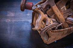 Set of vintage tools in wicker box on wooden board Royalty Free Stock Image