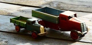 Set of vintage toys - trucks (lorries) toys on blue wooden background Stock Photos