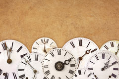 Set of vintage white clock faces against an old brown background Royalty Free Stock Photography
