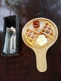 Set of waffle. With syrup and whipped cream on wooden board, stainless spoons and forks on white paper in black box on wooden table Stock Photo