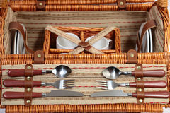Set of ware for picnic. Set for picnic in a basket. Consists of four plates, four glasses, four spoons, four plugs and four knifes Stock Photo