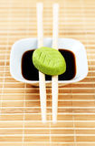 Set of wasabi and soy source on a bamboo tablecloth with wooden chopsticks Stock Images