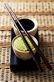 Set of wasabi and soy source on a bamboo tablecloth with wooden chopsticks Stock Photography