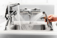 Set of water mixing faucets. With hand stock photography