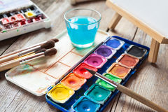 Set of watercolor paints, art brushes, glass of water and easel. With painting on old wooden table stock photography