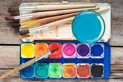 Set of watercolor paints, art brushes and glass of water on old Stock Photography