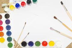 Set of watercolor paints, brushes for painting and blank white paper sheet of sketchbook. royalty free stock images