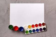A set of watercolor paints, cans with gouache and blank sheet of white sketchbook paper on a concrete background. Copyspace royalty free stock photos