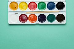 A set of watercolor paints on a green background royalty free stock photos