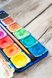 Set of watercolor paints on wooden background. Stock Photo