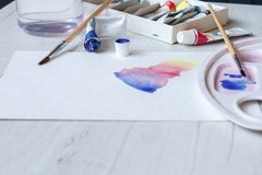 Set of watercolors, brushes, a glass of water and a palette on a white sheet, beautiful watercolor strokes royalty free stock photos