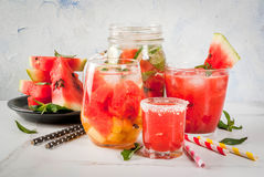 Set of watermelon summer drinks and cocktails: sangria, juice co. Oler cocktail, infused detox water, watermelon vodka shot. On a white marble table. Copy space Royalty Free Stock Photos